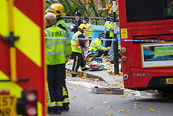 Ladbroke Grove, London, November 17th 2016. A double decker bus crashes into Kensal House on Ladbroke Grove prompting a major response from the emergency services including the air ambulance. According to Detective Chief Superintendent Ellie O'Connor of Met Police Kensington and Chelsea, 14 people including the driver were hurt, with none sustaining life-threatening or life changing injuries. Police officers would not speculate on the cause of the accident, but apologised for delays and commended all branches of the emergency services for their prompt and efficient response. The bus will be towed away for further investigations. PICTURED: Police talk with survivors in the aftermath of the accident.