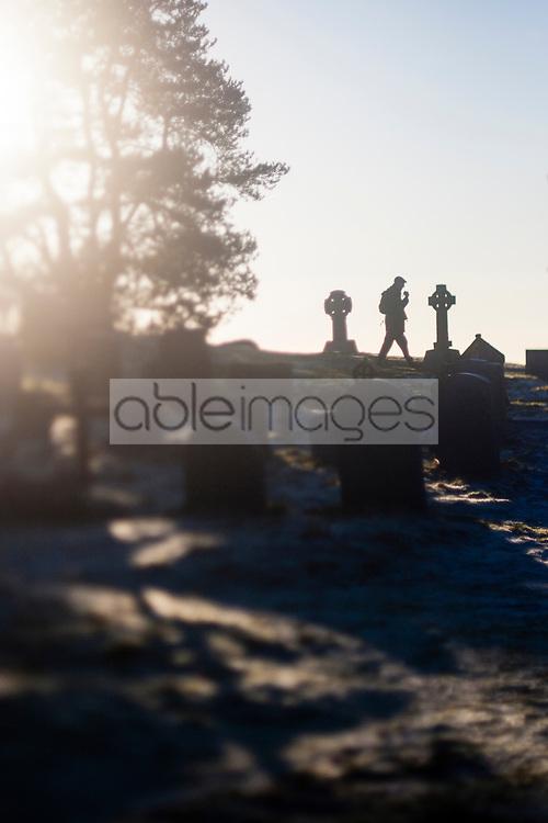 Silhouette of Man Walking through Graveyard