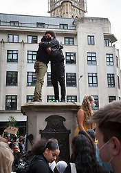 **Previously unseen pictures**<br /> © Licensed to London News Pictures; 07/06/2020; Bristol, UK. Protesters hug while stood on to the empty pedestal where a statue of Edward Colston was pulled down with a rope during a Black Lives Matter march through the city centre. The death of George Floyd, who died after being restrained by a police officer In Minneapolis, Minnesota, caused rioting and looting across the U.S.A and protests across the world. Photo credit: Mark Simmons/LNP.