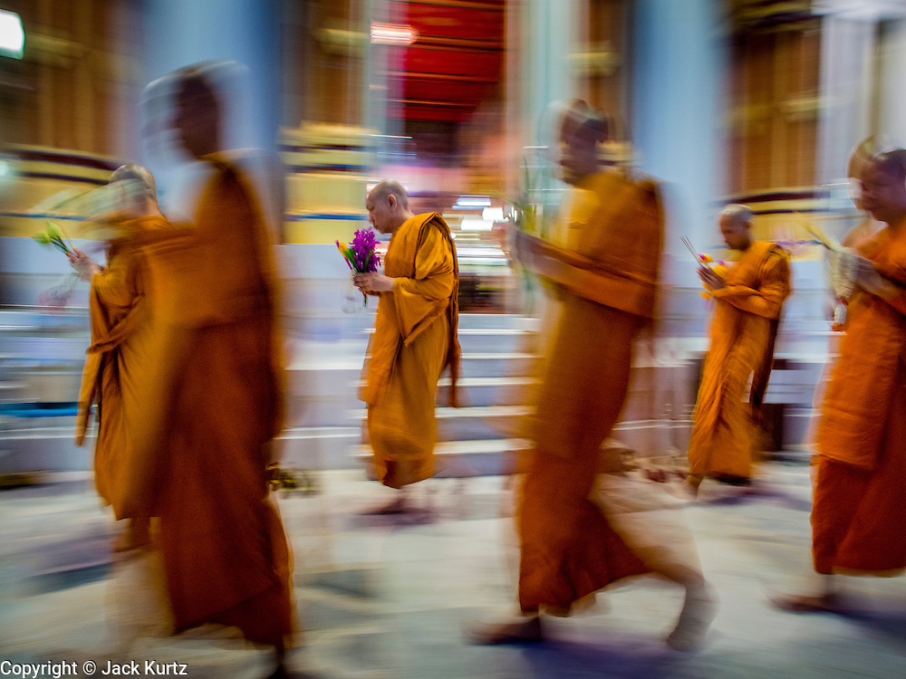 "13 MAY 2013 - BANGKOK, THAILAND: Buddhist monks walk clockwise around Wat That Thong during services on Vesak in the temple. Vesak, called Wisakha Bucha in Thailand, is one of the most important Buddhist holy days celebrated in Thailand. Sometimes called ""Buddha's Birthday"", it actually marks the birth, enlightenment (nirvana), and death (Parinirvana) of Gautama Buddha in the Theravada or southern tradition. It is also celebrated in Cambodia, Laos, Myanmar, Sri Lanka and other countries where Theravada Buddhism is the dominant form of Buddhism.     PHOTO BY JACK KURTZ"