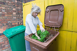 Woman putting garden waste in brown recycling bin,