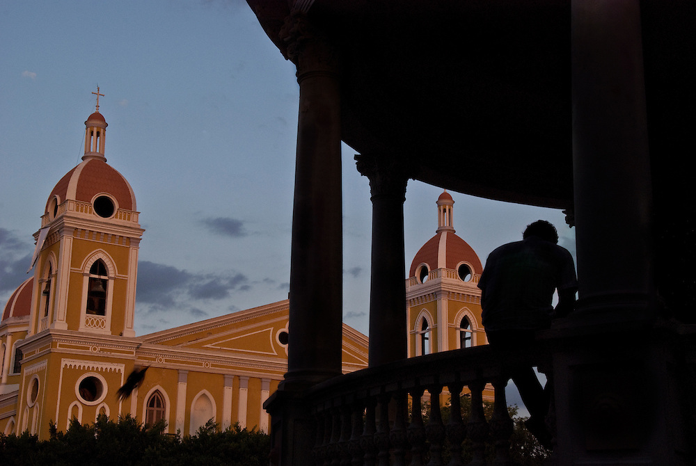 A man sits in the gazebo of the main square of Granada, Nicaragua.
