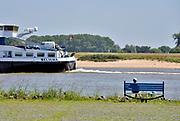 Nederland, Varik, 6-6-2018Een oudere man zit op een bankje bij de rivier en kijkt naar de schepen die voorbij varen . Hij is met zijn vrouw op de fiets een fietstochtje aan het doen .Foto: Flip Franssen