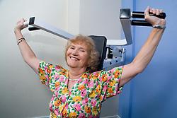 Women using shoulder press equipment in a YMCA gym,