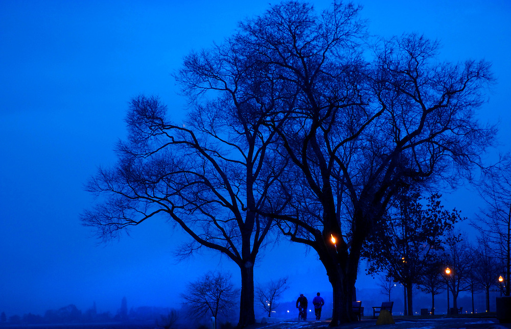 Pedestrians in Kelowna's City Park on a fog-shrouded February evening.