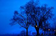 Pedestrians in Kelowna's City Park on a fog-shrouded February evening.