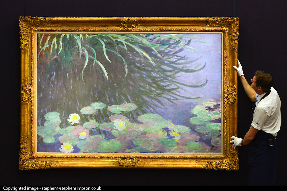 © Licensed to London News Pictures. 31/01/2013. London, UK An employee holds Claude Monet's .NYMPHÉAS AVEC REFLETS DE HAUTES HERBES. Expected to raise 12,000,000 -.18,000,000 GBP. Preview of highlights from Sotheby's forthcoming February sales of Impressionist & Modern Art and Contemporary Art in London, including works by Picasso, Bacon, Monet, Richter and Miró. Photo credit : Stephen Simpson/LNP