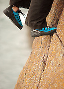 Two feet belonging to a rock climber wearing blue climbing shoes balanced on a warm coloured rock slab above th e sea.