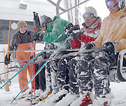 Boyne Highlands ski lift operator Rick Schmoldt (far left) helps opening day skiers onto the resorts Heather Express lift.