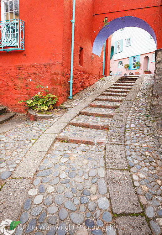 A cobbled path winds uphill and through a brightly painted arch, at Portmeirion, Gwynedd.