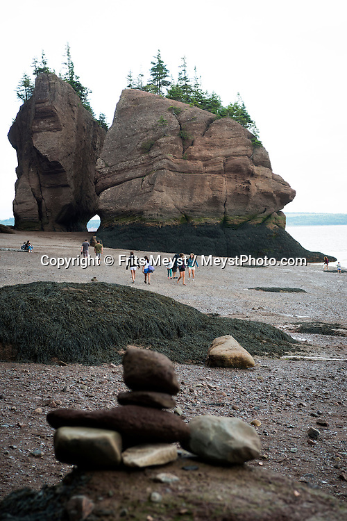 """New Brunswick, Canada, August 2014. The Hopewell Rocks.  As the tides drop in the Bay of Fundy, you get the chance to explore awe-inspiring rock formations. You walk along the beach, peering up at the giant """"flowerpots"""" towering above, and run your fingers along the rough striations created by the highest tides on Earth. New Brunswick province is part of historic Acadia, an early 17th century French land claim in North America. Governed by the British in the 19th century, Acadia was forcibly depopulated by the British and its inhabitants dispersed. Nowadays it is the only constitutionally bilingual province in the country. Photo by Frits Meyst / MeystPhoto.com"""