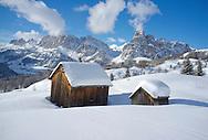 Mounts Lavarella, Conturines and Sasongher behind  snow covered wooden barns at the Alta Badia ski resort near Corvara, The Dolomites, South Tyrol, Italy
