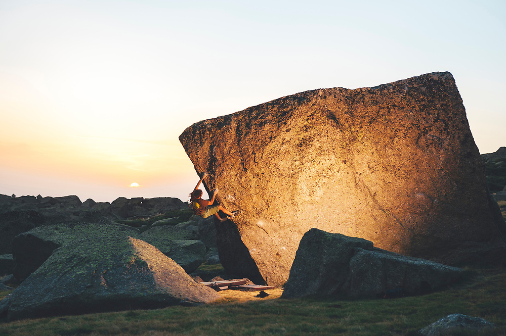 Rock climber contemplating next move on overhanging boulder problem at dramatic sunset in Hoyamoros, Spain