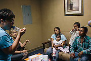 Asthma educator Sharon Borradori, left, shows Margarita Hernandez, center, and her husband, Severo Velasco, right, how their 2-year-old son, Mauricio Velasco will use an inhaler when he's older. Mauricio was recently released from the hospital after suffering from an extreme asthma attack. The family who doesn't speak English received help from Borradori with translation from Pastor Gladys Dias, second from left, from New Live Church.