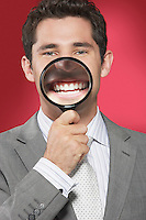 Man holding magnifying glass to smiling mouth against red background