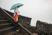 A man with umbrella in the rain at The Great Wall of China.