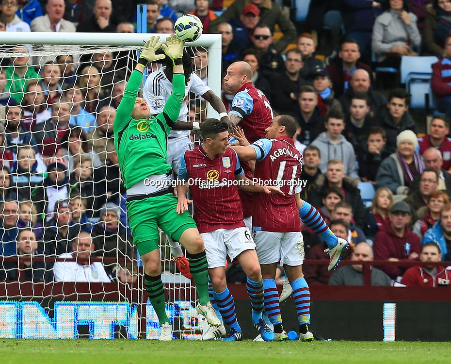 21st March 2015 - Barclays Premier League - Aston Villa v Swansea City - Aston Villa keeper Brad Guzan funbles under pressure from Bafetimbi Gomis of Swansea City - Photo: Paul Roberts / Offside.