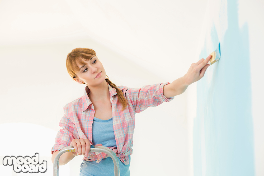 Woman on ladder painting wall with paintbrush