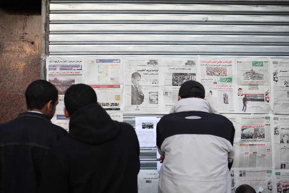 Protesters at Tahrir Square read newspapers taped to a wall, 9 February.