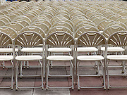 rows of empty white plastic folding chairs