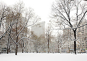 The Flatiron Building as seen from Madison Square Park in winter snow, New York City.