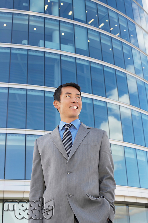 Businessman standing hands in pocket Outside Office Building