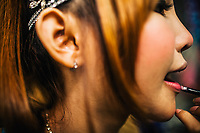 Ant applies lipstick backstage at her music club. Ant is a 21-year-old ladyboy singer living in Bangkok, Thailand.