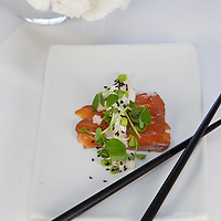 Gravlax topped with a white mustard sauce and garnished with fresh pea shoots served with black chopsticks on a white plate. Food styled by Laura Prentice.