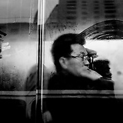 A man is looking through the window of a bus.