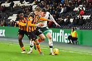Barnsley FC player Kieffer Moore (19)  under attack from Hull City defender Michael Dawson (21) and Hull City defender Ola Aina (34) during the EFL Sky Bet Championship match between Hull City and Barnsley at the KCOM Stadium, Kingston upon Hull, England on 27 February 2018. Picture by Ian Lyall.