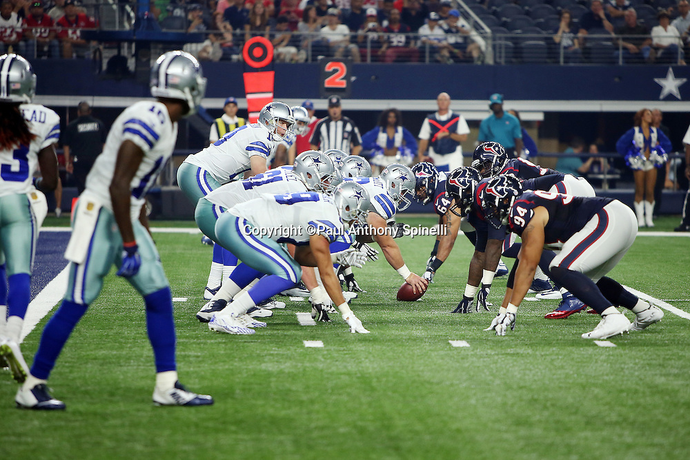 The Dallas Cowboys offensive line gets set to snap the ball at the line of scrimmage opposite the Houston Texans defensive line during the 2015 NFL preseason football game against the Dallas Cowboys on Thursday, Sept. 3, 2015 in Arlington, Texas. The Cowboys won the game 21-14. (©Paul Anthony Spinelli)