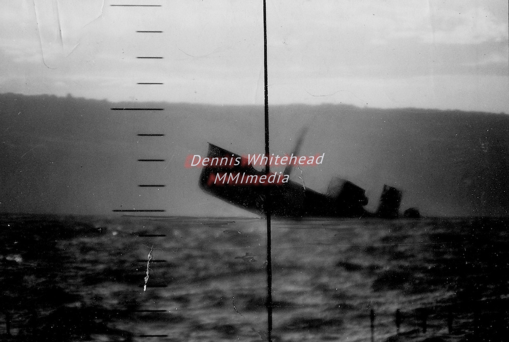 A photograph taken through the periscope ahows a Japanese freighter sinking after being topedoed by a U.S. submarine.