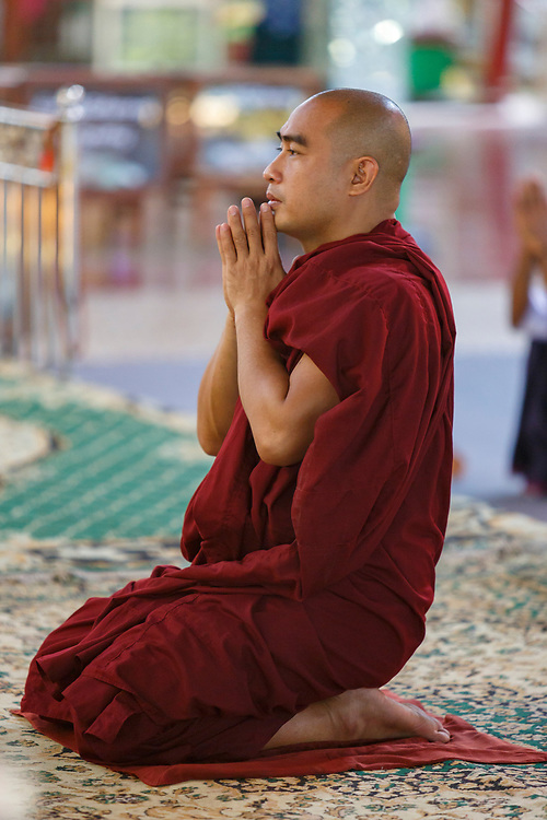 Monk at prayer in one of the temples in Yangon, Myanmar
