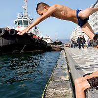 A bot dives into the Bay of Izmir along Kordon walkway in Izmir, Turkey.
