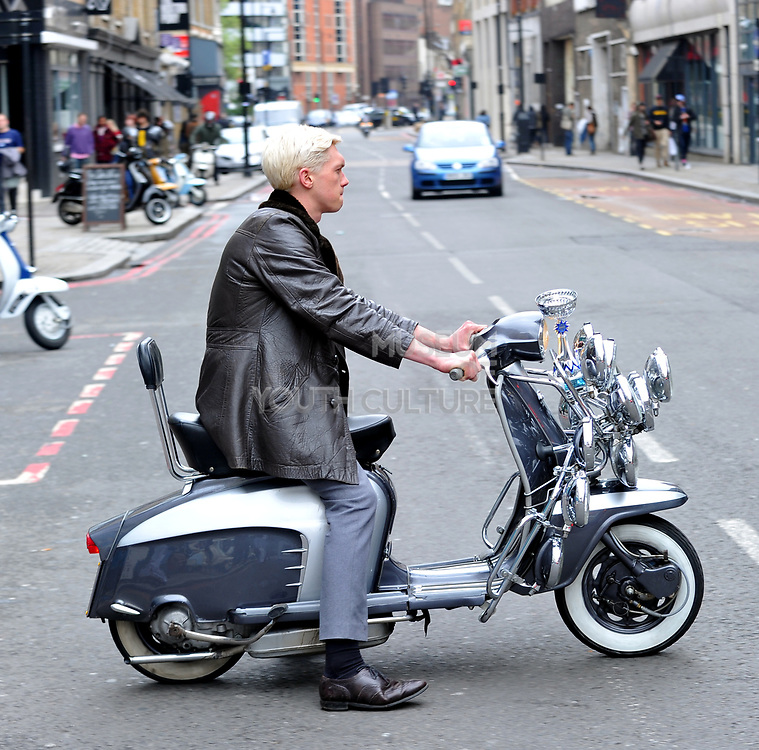 Mod sitting on his scooter in profile, London, UK, 2010