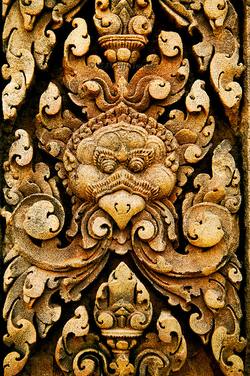 Detail of a relief of the red sandstone sculpture that completely covers the temple of Banteay Srei, Angkor.