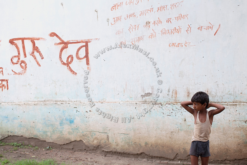 In the early morning, a lone boy is standing by Hindu writing on a wall near Sersiya Kekrahi village, Varanasi District, Uttar Pradesh, India. In 2012, Kanchan (name changed) went with a friend to bring lunch to her father, around 2 km away from her home. On the way they met Rajesh (rapist) and Ashok, a friend of his. Both girls were picked up on the spot using an excuse. Ashok drove Kanchan's friend home, but Rajesh forced Kanchan to travel with him during six days and for hundreds of kilometres across different states. (Mirzapur / Chennai / Itarsi / Bhusawal) He raped her once behind the station in Itarsi. With great effort and some coincidence, the uncle of Kanchan managed to bring her back home. Although she was scared, she insisted on going to the police to file a case (FIR). She was kept at the police station for 12 days and threatened to prevent her from filing an official case. Ashok and Rajesh are from higher caste and wealthy families. While Rajesh spent 24 days in jail initially in summer 2012, he is now a free man while the trial is still going on. Kanchan's family is now struggling to put together 30.000 Indian Rupees (500 USD) to continue battling for justice in court.