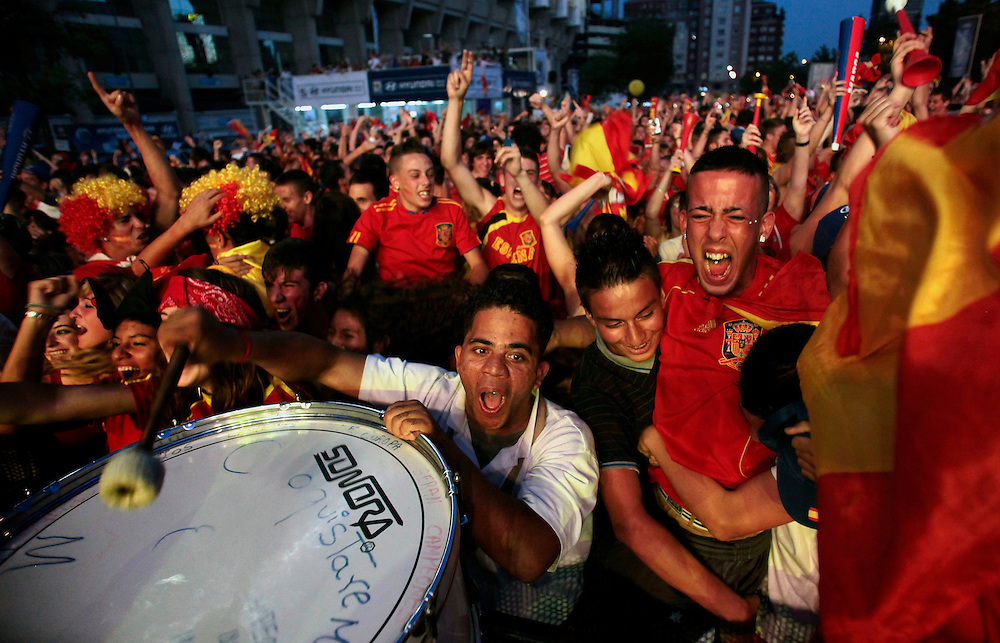 Fans react after Spain scored during the World Cup quarterfinal soccer match between Spain and Paraguay, on a large screen outside the Santiago Bernabeu stadium in Madrid, on Saturday, June 3, 2010. Millions of people worldwide are following the World Cup soccer tournament which is been held in South Africa, and broadcast to a diverse community of football fans. Spain won 1-0.