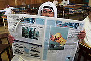 At a large coffee shop where men lounge about, smoke, and drink coffee and tea, a man reads a newspaper about the USA invasion of Iraq on March 23, 2003. Kuwait City, Kuwait. (Supporting image from the project Hungry Planet: What the World Eats.).