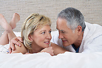 Middle-aged couple lying on bed talking