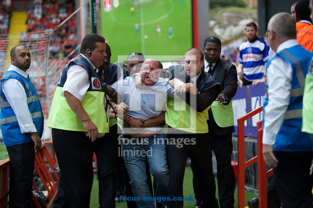 A fan of Queens Park Rangers is escorted off by the stewards during the Sky Bet Championship match at The Valley, London<br /> Picture by Alan Stanford/Focus Images Ltd +44 7915 056117<br /> 08/08/2015
