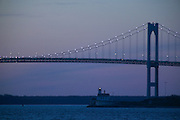 USA - Newport, RI - Newport Pell Bridge and Rose Island lighthouse at dusk.