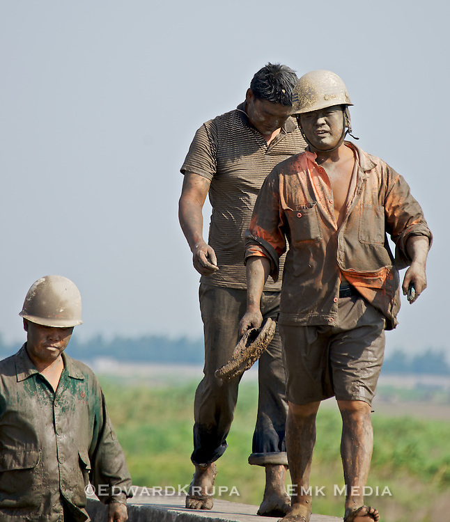 Muddied workers walking after setting up a sentiment diversion pipe used to pump tidal sediment from the South China Sea to a more desirable location near Wenzhou in Zhejiang province.