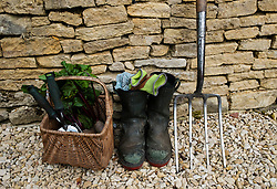 Detail of gardeners tools and boots in an English garden