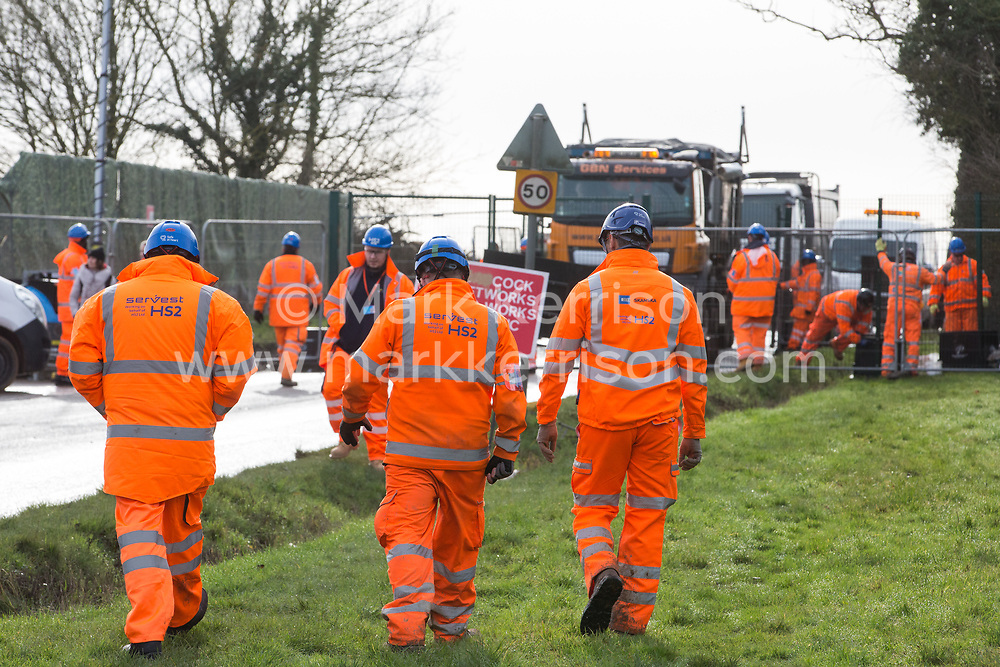 Harefield, UK. 8 February, 2020. HS2 engineers walk alongside Harvil Road in the Colne Valley where tree felling work for the high-speed rail link has been scheduled. A road closure appears behind.