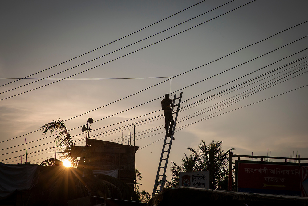 A man stands at the top of a tall ladder and works on the electricity line at sunset in Cox Bazar, Chittagong Division, Bangladesh, Asia.   (photo by Andrew Aitchison / In pictures via Getty Images)