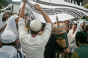 A new Torah Scroll is brought into a synagogue while the onlookers celebrate the event with dances and songs