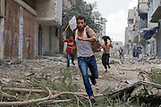 Palestinian men  run with a white flag in the Shejaia neighbourhood, which was heavily shelled by Israel during fighting, in Gaza City July 20, 2014. At least 50 Palestinians were killed on Sunday by Israeli shelling in the Gaza neighbourhood, and thousands fled for shelter to a hospital packed with wounded,while bodies were unable to be recovered for hours until a brief cease fire was implemented . (Photo by Heidi Levine for The National).