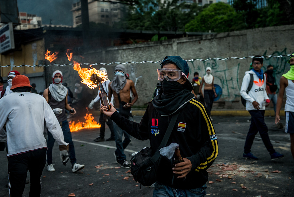 CARACAS, VENEZUELA - JUNE 2, 2017:  Anti-government protesters hurl stones and molotov cocktails <br />