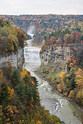 "From Inspiration Point, see Middle and Upper Genesee Falls amid the splendor of autumn leaf colors, at Letchworth State Park, near Portageville, New York, USA. In Letchworth State Park, renowned as the ""Grand Canyon of the East,"" the Genesee River roars northeast through a gorge over three major waterfalls between cliffs as high as 550 feet, surrounded by diverse forests which turn bright fall colors in the last three weeks of October. The large park stretches 17 miles between Portageville and Mount Morris in the state of New York, USA. Drive or hike to many scenic viewpoints along the west side of the gorge. The best walk is along Gorge Trail #1 above Portage Canyon from Lower Genesee Falls (70 ft high), to Inspiration Point, to Middle Genesee Falls (tallest, 107 ft), to Upper Genesee Falls (70 ft high). High above Upper Falls is the railroad trestle of Portageville Bridge, built in 1875, to be replaced 2015-2016. Geologic history: in the Devonian Period (360 to 420 million years ago), sediments from the ancestral Appalachian mountains eroded into an ancient inland sea and became the bedrock (mostly shales with some layers of limestone and sandstone plus marine fossils) now exposed in the gorge. Genesee River Gorge is very young, as it was cut after the last continental glacier diverted the river only 10,000 years ago. The native Seneca people were largely forced out after the American Revolutionary War, as they had been allies of the defeated British. Letchworth's huge campground has 270 generously-spaced electric sites."